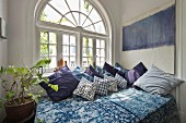 Comfy bed and house plant in front of arched French window