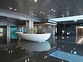 Luxurious hotel reception lobby area with recessed lights reflecting on floor