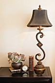 Lamp, books, clock and vase on console table against wall