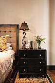 Kommode als Nachttisch neben Bett mit antiker Tischleuchte