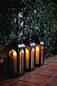 Close-up of candle lanterns in a row on tiled floor by plants
