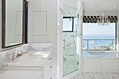 Luxury bathroom in white with washbasin, shower room and a separated shower; sea view