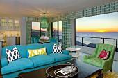Sitzecke vor Fensterfront mit Blick auf Sonnenuntergang über dem Meer