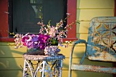 Rustic chair by flower arrangement on table on porch