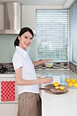 Smiling young woman cutting lemons in kitchen