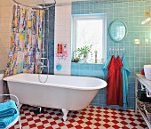 Colourful shower curtain behind retro bathtub, blue and white wall tiles and red and white chequered floor tiles