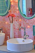 Modern countertop sink with retro tap fitting and oval mirrors with turquoise frames on toile de jouy wallpaper with fairy lights