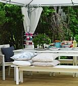 Dessert buffet on white table beneath tent-style gazebo on terrace