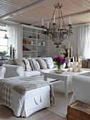 Ottoman and white sofa around coffee table below wrought iron candle chandelier hanging from wooden ceiling in rustic living room