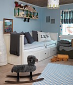Rocking sheep next to pastel blue and white checked rug in front of white single bed with tall backrest, foot and headboard