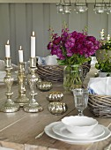 Lit candles in silver candlesticks on set table in rustic interior