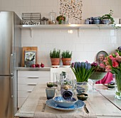 Gedeckter Tisch mit blau-weißem Geschirr und Frühlingsblumen; Küchenzeile mit Kräutertöpfen im Hintergrund