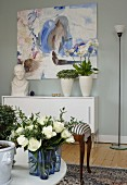 Blue glass vase of roses on coffee table, houseplants and bust on sideboard below modern artwork in background