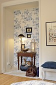 Table lamp, lantern and silver bowl on antique table in niche with floral wallpaper above fawn figurine on denim cushion