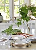 Geschirr und Gläser vom Flohmarkt, Rhabarber und Flieder auf weißem Esstisch