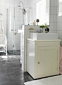 Rustic washstand against half-height wall in white-tiled bathroom