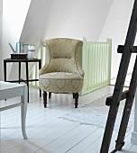 Antiker Sessel mit Ornament-Muster auf Bezug vor Treppengeländer im Dachzimmer mit weißem Dielenboden