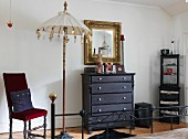 Gilt-framed mirror above chest of drawers, antique chair and decorative parasol in bedroom