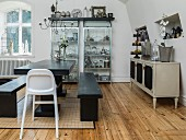 Dining table and benches made from black-painted wood, highchair, antique-style sideboard and modern display cabinet in background