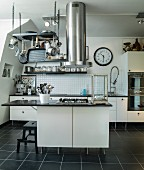 Extractor tube and cooking utensils hanging from grille above island with cooker in black and white, modern kitchen