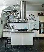 Dunstabzugsrohr und Gitter mit Kochutensilien über Herdblock in schwarz-weisser, moderner Küche