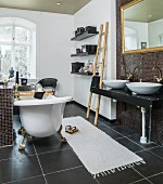 Antique, free-standing bathtub, washstand and gilt-framed mirror in black and white bathroom with ornaments and accessories