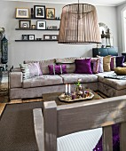 Sand-coloured sofa with purple scatter cushions below floating shelves on grey-painted wall