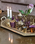 Coated glass beakers, candlesticks and ornate metal jug and teapot on embossed tray