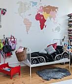Weltkarte mit verschiedenen Mustern über einem Kinderbett aus Metall