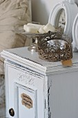 Vintage, hand-crafted metal wreath next to soap in silver-coloured bowl on shabby-chic bedside cabinet