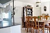 Essplatz mit Stühlen und Tisch aus der Gründerzeit und Vintage Pendelleuchte in ländlicher Küche