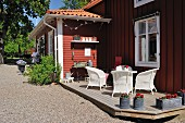 Sunny terrace with white wicker armchairs and vintage planters outside traditional Swedish house