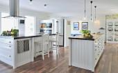 Grosszügige Küche im Landhausstil, mit freistehendem Küchenblock und Edelstahl Dunstabzug