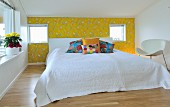 Double bed with headboard, white bed linen and colourful scatter cushions against accent wall with yellow, bird-patterned wallpaper; white designer chair to one side