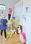 Girls playing in child's bedroom with ladder leading to raised sleeping area, yellow desk and soft toys on floor