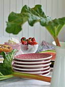 Stacked plates amongst rhubarb leaves, cakes and bowl of strawberries on table set for afternoon tea