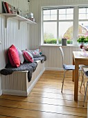 Sitzbank mit Fellen und Kissen im Esszimmer mit weisser Holzverkleidung an der Wand