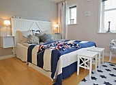 Maritime bedroom with blue and white striped bedspread and crocheted Stars and Stripes blanket on double bed