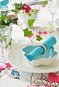 Turquoise linen napkin with napkin ring on white bowl on floral tablecloth