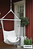 Hammock chair next to lantern and olive tree on veranda of Swedish house