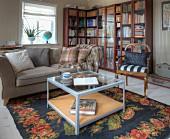 Coffeetable auf Teppich mit Blumenmuster, Sofa und Antikstuhl vor Übereck-Vitrinenschrank mit Bibliothek