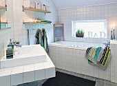 Washstand and tub in white-tiled bathroom with window