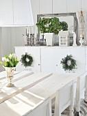 weiße Tulpen in Silberkelch auf rustikaler, weisser Tischplatte; mit Kerzen, Pflanze & Spiegel dekoriertes Sideboard im Hintergrund