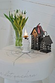Vase of tulips, oil lamp and miniature house on white-painted tree stump stool with decorative lettering