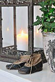 Worn child's shoes used as ornaments in front of antique lantern and potted ivy
