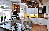 Table with painted chequered top and wicker chairs in country-house kitchen-dining room with baskets hanging from ceiling