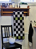 Chequered towel on towel rail with ornaments on wooden shelf above black-painted wooden chair