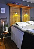 Old farmhouse cupboard doors with wall lamps used as headboard of double bed; hand-crafted metal chair used as bedside table