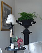 Table lamp with white lampshade on round side table, and foliage plants in black, antique urn on plinth in background