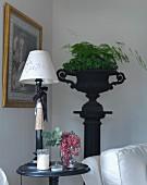 Tischleuchte mit weißem Schirm auf rundem Beistelltisch, im Hintergrund Stele mit antik griechischem Metall Pflanzengefäss in Schwarz und verschiedenen Grünpflanzen
